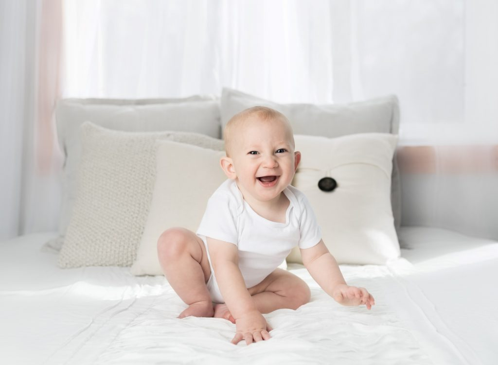 Baby on a mattress smiling